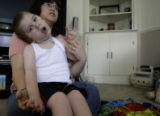 Cindy DeSplinter(cq) holds her special needs son Micah(cq), 5, in their home in Thornton, Colorado...