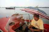 Ted Zen (cq) waits in his boat for his son to arrive at a dock off of  Sloan's Lake, while the...