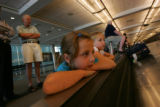 Caty Ogden, 6, Emily Ogden, 9, both of San Antonio, Texas, wait for their bags to arrive at Denver...