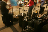 Passengers wait for their bags to arrive at carousel 2 at Denver International Airport on Monday,...