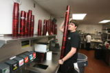 Bryan Malinoski, (cq), a server assistant, takes a load of clean glasses to from the kitchen....