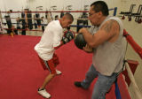 Robert Rodriguez,17, left, punches a medicine ball held by his father and coach, Jeff Rodriguez...
