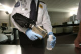 Baggage TSO employee, Nathan Voith (cq) demonstrates to the press how a liquid explosive detection...