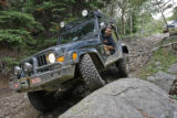 DU Off-Road Club President Peter Belsky (cq) drives his 2002 Jeep TJ onto a sizable rock...just...