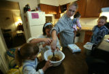 Aubrey Stacy (cq) carrying 9 month old Mable Smith stirs the crust as son, Elias Stacy, 9 (r) and...