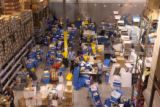 Workers scan articles at the final stop before packaging and shipping at the warehouse of...