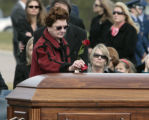 Mary Hancock, left, puts a rose pedal on her son's casket, Major John L. Carroll, during graveside...