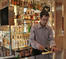 Paul McGee (cq), Corporate Mixologist for Wolfgang Puck, gets the bar ready for business, Tuesday...