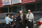 A young man, is escorted by police investigators for questioning, as CSI members investigate the...