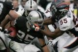 0251 Denver Broncos D.J. Williams tries to pull down Oakland Raiders Justin Fargus in the first...