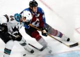 The Colorado Avalanche's Ryan Smyth, right, fights for the pucks against San Jose's Marc-Edouard...