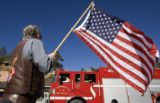 DM3281   Jerry Lautigar, 63, of Evergreen waves a flag for the troops of the 3rd Brigade, 4th...