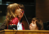 Tommie Burris, 4 is held by her mother, Bonnie Burris with Bonnie's sister Judy Kuhn  stand at the...