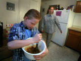 Elias Stacy, 9 helps mom, Aubrey Stacy  make a pecan pie for Thanksgiving in Arvada, Colo. on...