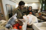 0102 Partners Nita Mosby-Henry, left, and Carla Harvard, right wort together as they decorate a...