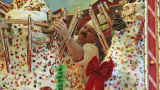 Executive Chief Kevin Goodwin does some final adjustments on his holiday gingerbread house,...