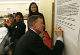 Mayor John Hickenlooper signs the Cole contract, his agreement to pay the unmet costs of college...