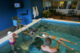 Swimming instructor Jonathan McCoy (cq), (back to camera) helps swimmer Ainsley Woo (Cq), 4, float...