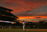 Dave Collins, first base coach for the Colorado Rockies takes the field as the sun sets on Coors...