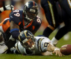 (Denver, Col, September 26, 2004)  Chargers quarterback reaches for the ball after being sacked by...
