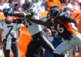(DENVER, COLO., SEPTEMBER 26, 2004) - Denver Broncos' #56, Al Wilson, right, stride for stride...