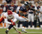 (DENVER, COLO., SEPTEMBER 12, 2004) - Denver Broncos #22-Quentin Griffin, right, trys to pull away...