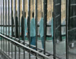 A pedestrian's reflection is shown in the walls of the Dry Creek Pedestrian Bridge, which...
