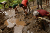 A villager takes a drink from spring water as coworkers continue to dig out an area that will be...