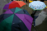 DLM0130  RTD riders wait under umbrellas showing a rainbow of colors on the 16th Street Mall in...