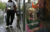 DLM0224  Kimberly Johnson, 14, right, waits inside a Starbuck's for the rain to stop on the 16th...