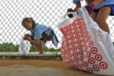 DLM0434  Megan Schmitt, 10, from left, and Jessie Murphy pick up trash in dugout of the baseball...