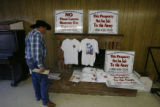 "DLM0374  Rancher Tim Roberts picks up some bumper stickers that say ""This property is not for..."