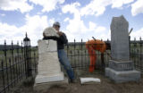 Walter Gallegos (cq) puts the top of the cracked headstone back on Dario Gallegos' grave in the...