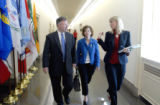 Rep. Doug Lamborn, R-Colo., left, is briefed by staff Melissa Carlson, right, as he walks to a...