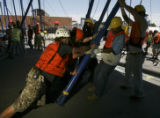 Workers grabbed and pushed and pulled and groaned and grimaced getting the poles into place. The...