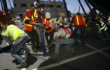 center low, Conrad Danley, 54, (cq), in american flag hard hat pulls with the group putting their...