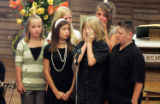 Kaeden Von Duyke wipes away tears as he, his sister and cousins sing the song...