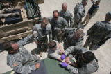 (From left) Staff Sergeant Bennett (cq) holds the Saline bag as Specialist Squelch (cq) gets...