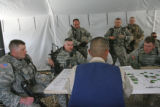"Major Andrew Olmsted and his unit sit in a tent, as they listens to a ""role-player"" (at..."