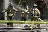 Firefighters use water to decontaminate each other during a fire at Circuits West in Longmont,...