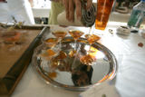 1489 Tommy Bahama Rum is poured over a tangerine at the Grand Tasting Pavilion Courtyard during...