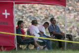 Friends and family wait under a tent as members of the Littleton Fire and Rescue and State Park...