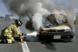Evergreen volunteer firefighter Mike Mendelsohn (cq) tries to control a car fire on HWY 74 in...