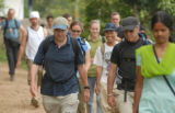 Bernard Amadei (left) and Barry Bialek (second to right) lead a hike around the village of...