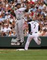 Rockies Kasui Matsui beats out an infield hit, as Mets first baseman Carlos Delgado goes up for...