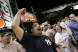 Dimitri Valerga (cq) of Thornton, Colo., cheers on the Yankees to no avail as Rockies fan Arlene...