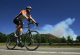 A biker from Ride the Rockies cruises past a plume of smoke from a back fire near New Castle,...