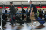 United Airline passengers make their way through the check-in line Wednesday morning June 20,...
