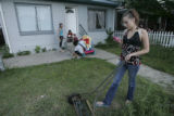 Guadalupe Mata (cq), 13, of Denver, Colo., sends a friend a text message while mowing the grass at...