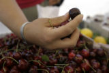 Renee Sweet (cq) picks through cherries from the Fruit Stand Inc. at the Cherry Creek Fresh Market...